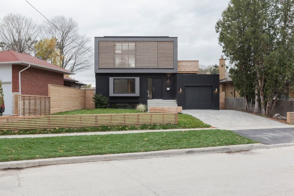 A modern home's small front yard featuring a well-maintained lawn area with a wooden fence.