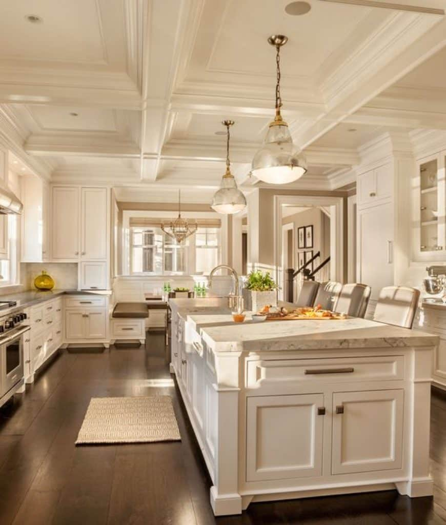 Large kitchen filled with white cabinetry and breakfast island along with a window seat nook at the far end. It is illuminated by pendant lights that hung from the coffered ceiling.