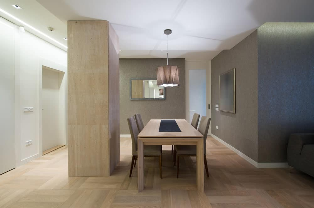 This dining area features stylish hardwood flooring and gray walls. The dining table set is lighted by a modish pendant lighting.
