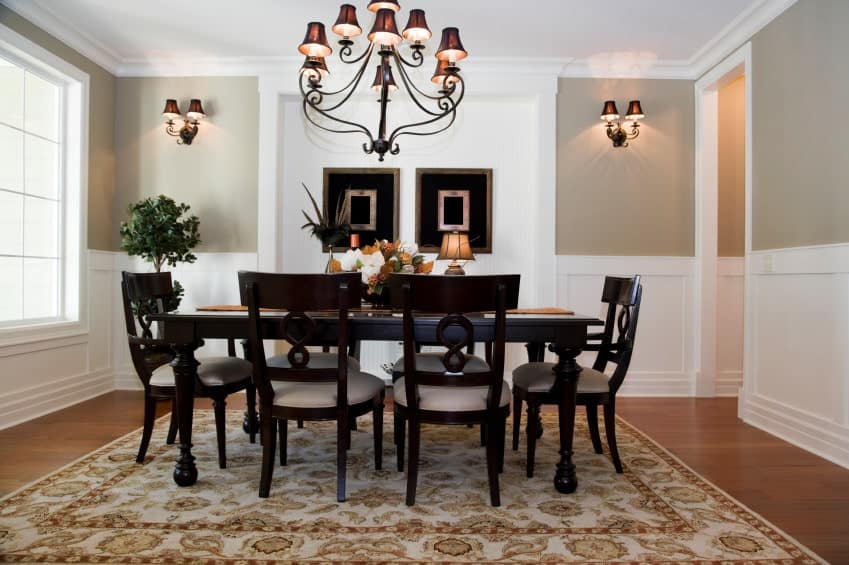 A classy dining room featuring a large area rug and is lighted by a glamorous chandelier.