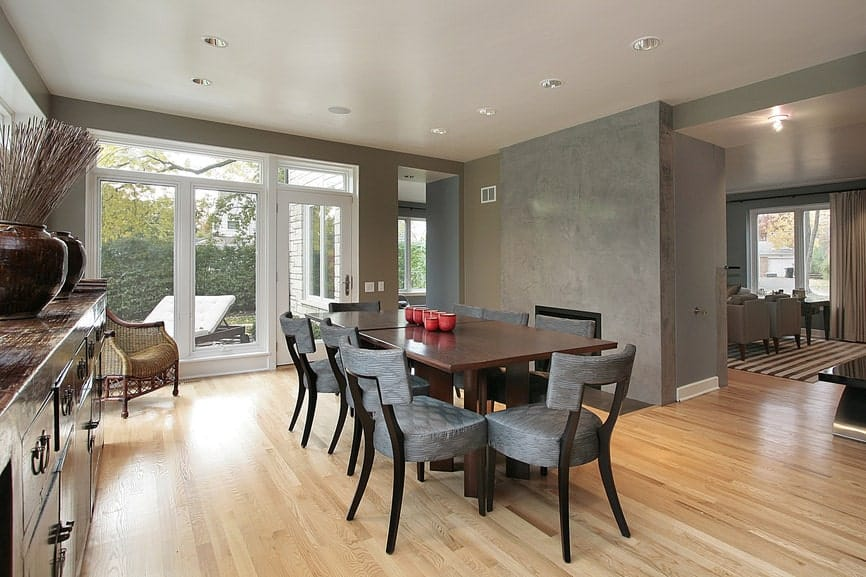Spacious dining area featuring a wooden dining table paired with gray seats set on the hardwood flooring and is surrounded by gray walls.