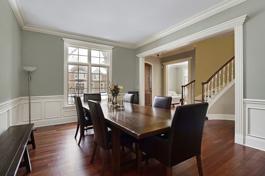 This dining area features gray walls and hardwood floors. It also features a rectangular dining table set along with a bench seating at the side.