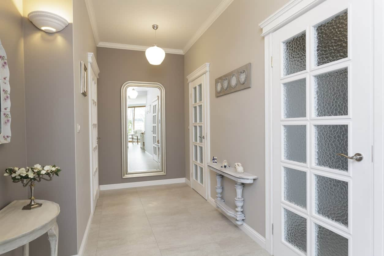 Small foyer featuring tiles flooring and gray walls lighted by a pendant light and a wall sconce.