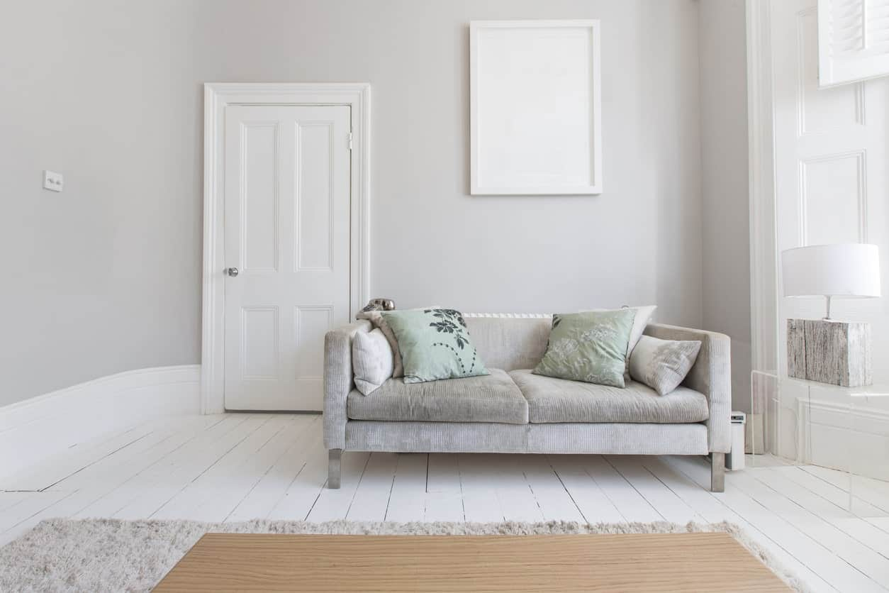 This is a simple and bright foyer with light gray elements that are subdued by the white hues that lighten the gray further. The only places that you will see the difference are at those areas where the gray and white meet like the white frame on the gray wall, the white door against the gray wall and the gray couch against the white flooring.
