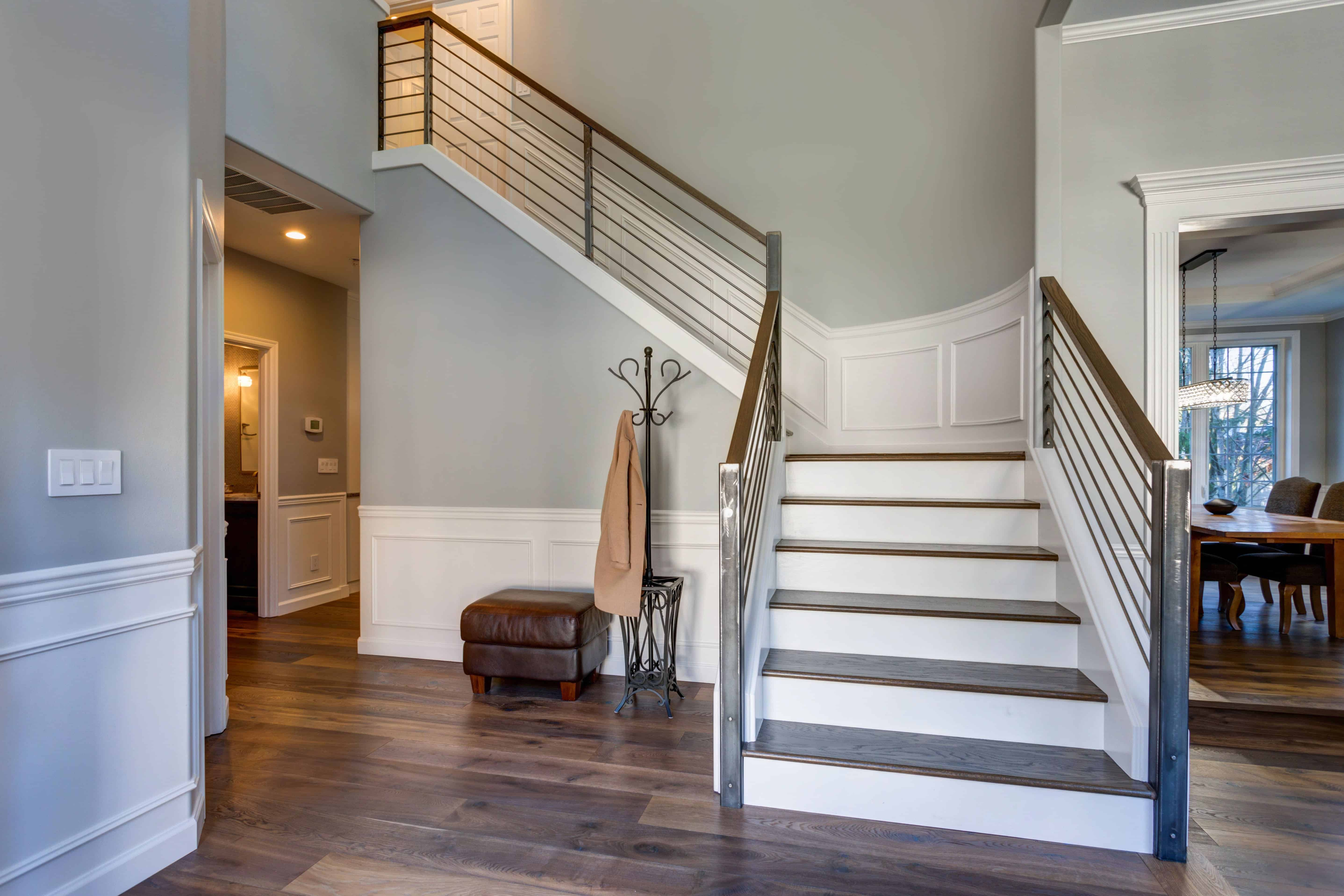 The gray walls of this elegant foyer have white wooden finishings on the bottom half that is contrasted by the hardwood flooring and the small cushioned chair beside the dark iron coat rack with an umbrella rack at the bottom.