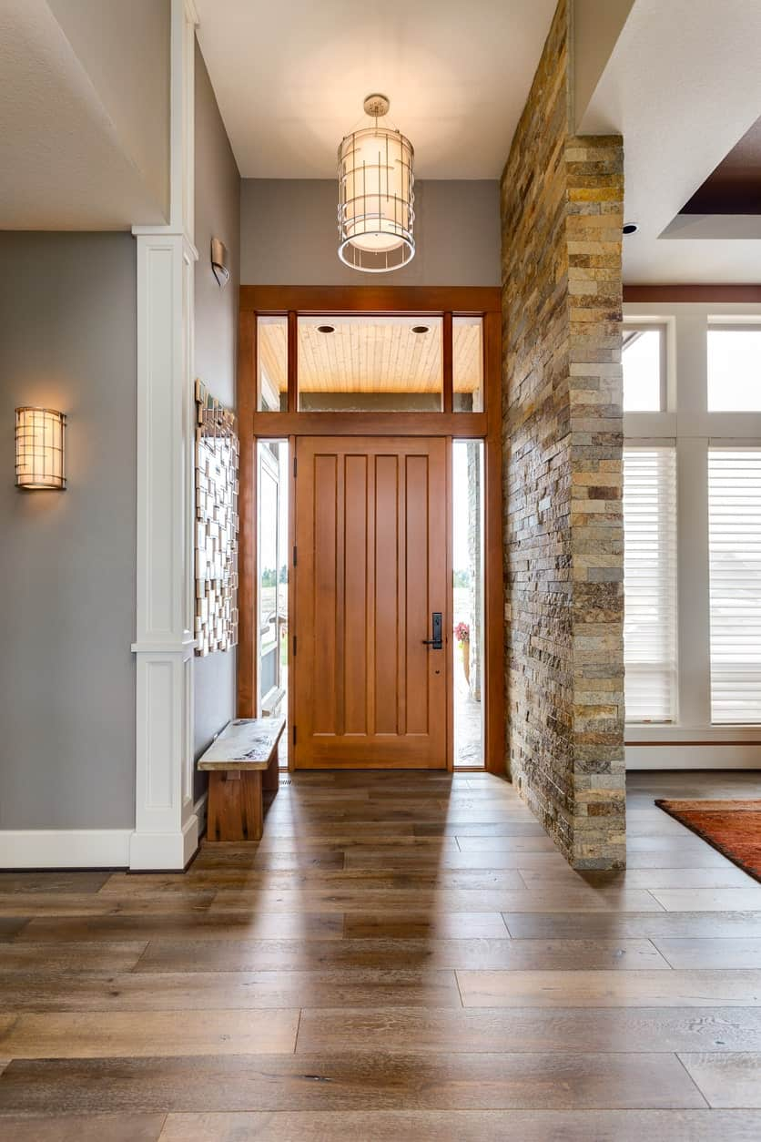 The wooden main door is adorned by matching sidelights and a large transom window above that bring in natural light coming from outside. The door pairs well with the wooden bench placed against a gray wall that has a wall-mounted art.