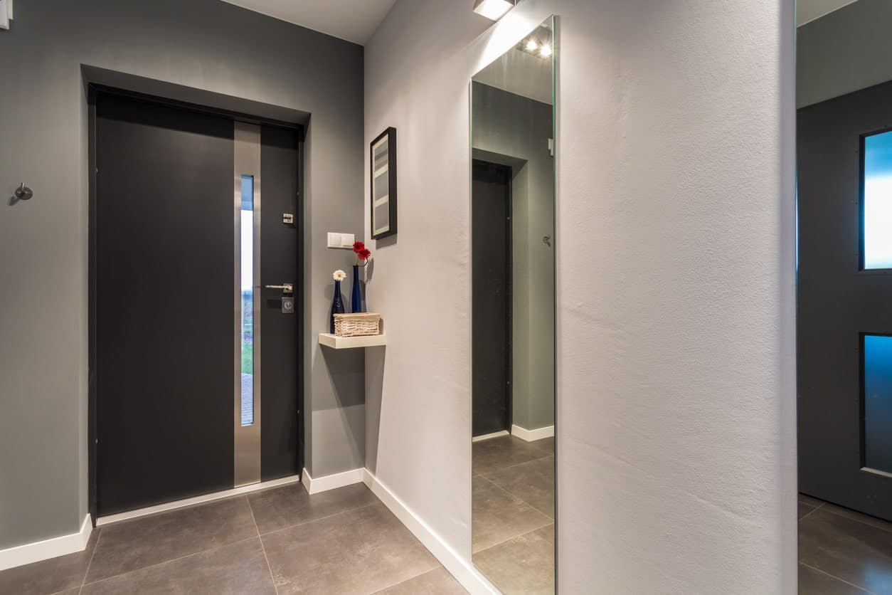 This simple foyer has a minimalist spirit to it with its bare gray walls adorned with a single mirror. The gray walls and flooring perfectly complement the modern main door that has a dark gray hue. Beside the door is a corner shelf with simple decorations on it.