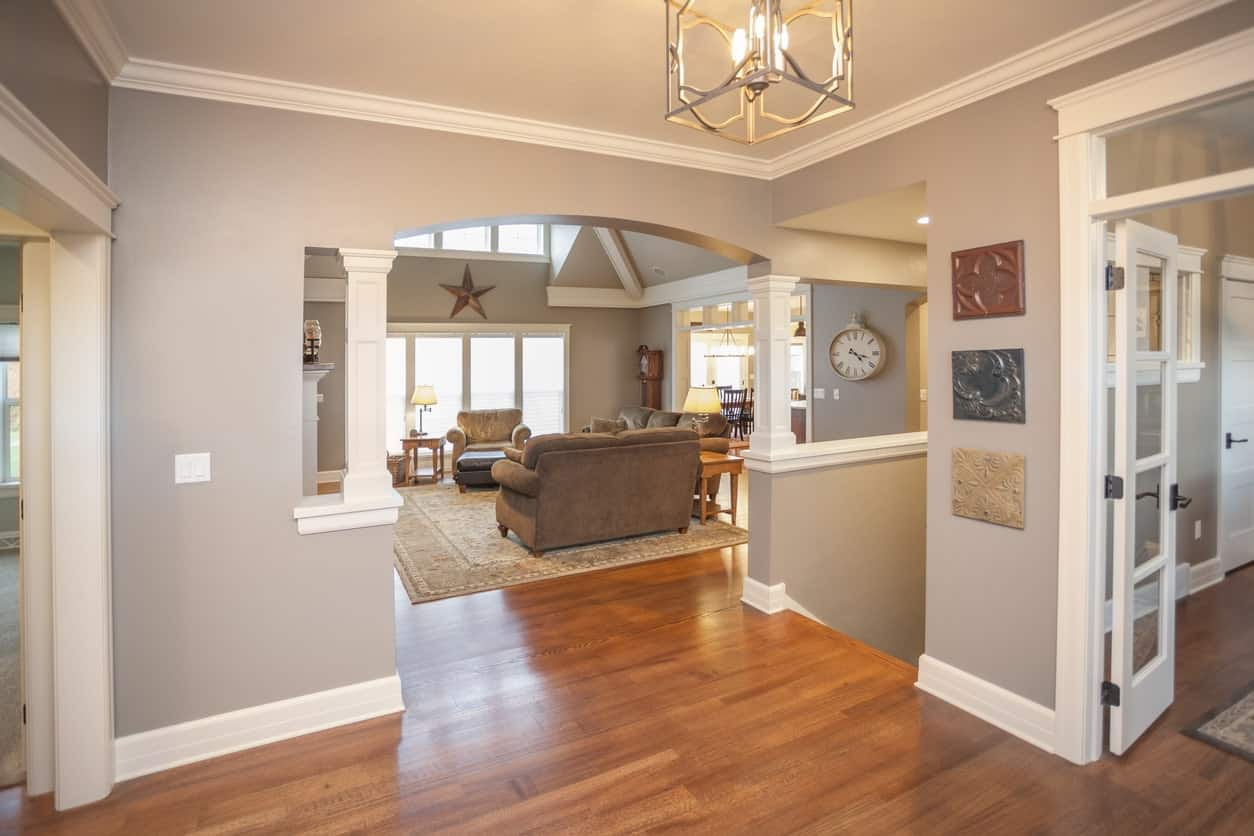 This is a warm and welcoming foyer that has a homey hardwood flooring that complements the gray walls and its white linings and moldings. From this foyer, you can clearly see the living room through an arched entryway with small white columns on each side.