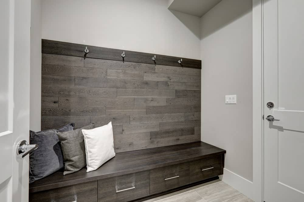 This simple and small foyer is dominated by a large wooden structure that serves as a mudroom with built-in drawers at the bottom for the shoes and hooks at the top for the coats and hats. This contrasts the gray walls and ceiling.