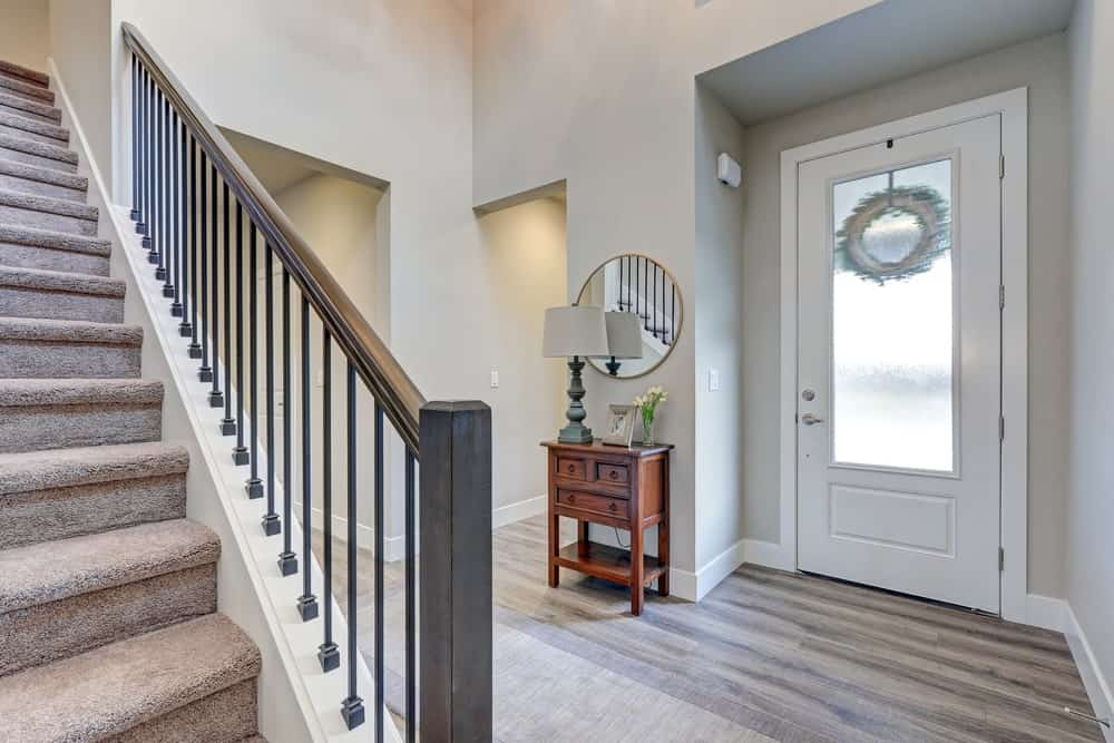 The gray walls of this high-ceilinged foyer are brightened up by the natural light coming in from the frosted glass panel of the white wooden main door. The gray walls are contrasted by the hardwood flooring and the small console table with mini drawers.