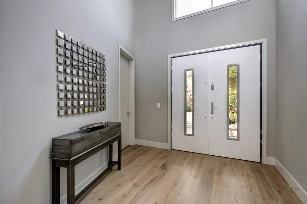 The wooden console table against the gray wall is paired with a peculiar small set of mirrors that serve as a wall-mounted artwork. The light gray walls perfectly match with the white double doors that have a couple of slat-like windows in the middle.