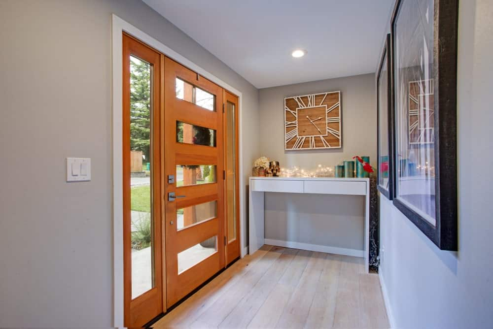 Small foyer featuring hardwood flooring and gray walls, along with an orange door.