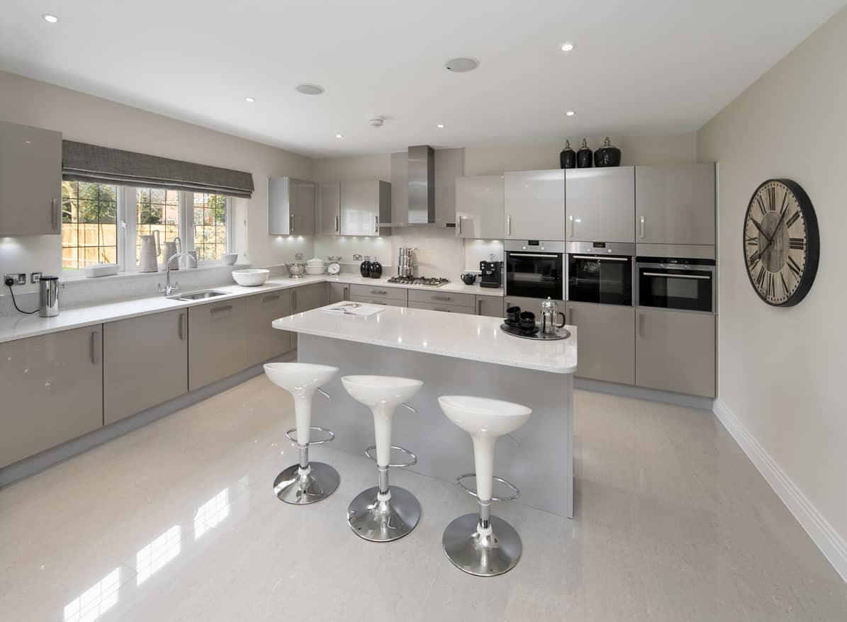 A simplistic kitchen featuring gray kitchen counters and breakfast bar island with white countertops.