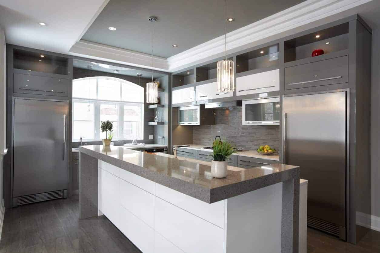 This kitchen features a stylish center island lighted by a pair of pendant lighting set on the tray ceiling.