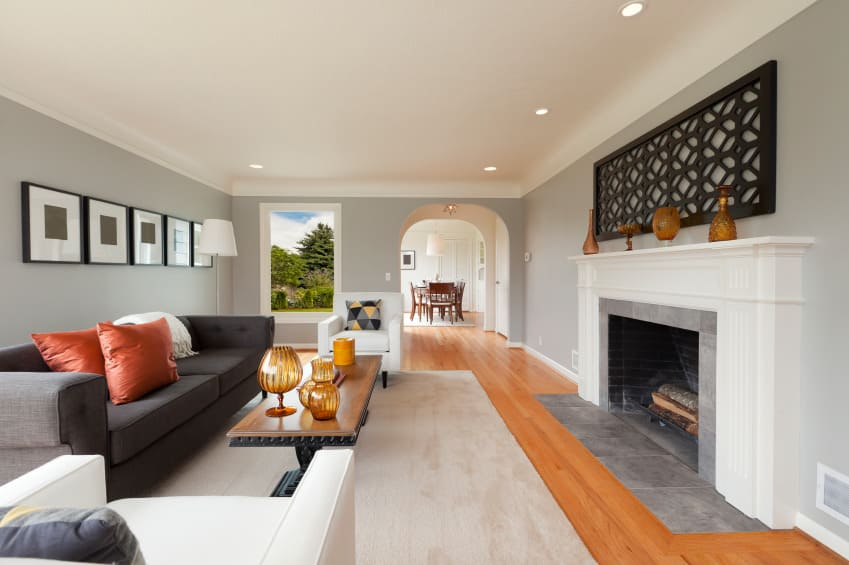 Spacious living room featuring a gray sofa set and a large area rug covering the hardwood flooring. The room also offers a large fireplace.
