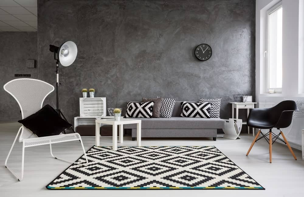 The charming black and white patterns of the area rug matches with the throw pillows on the comfortable gray couch. This couch is paired with an assortment of wooden furniture like a white crate side table, white wooden coffee table and a pair of contradicting chairs. All of this is against a massive gray wall for a background.