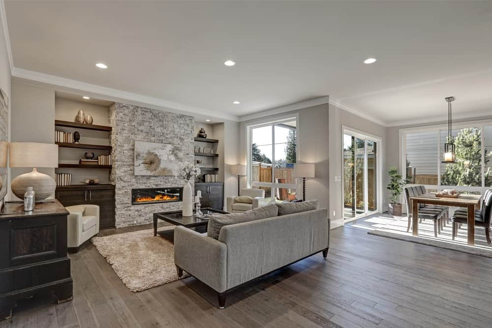 This is a warm and welcoming living room that has different textures all brought together by the gray hues. The gray couch is facing a modern fireplace that is inlaid in a massive wall-high rough gray stone structure that is flanked by two wooden structures built into the gray walls.