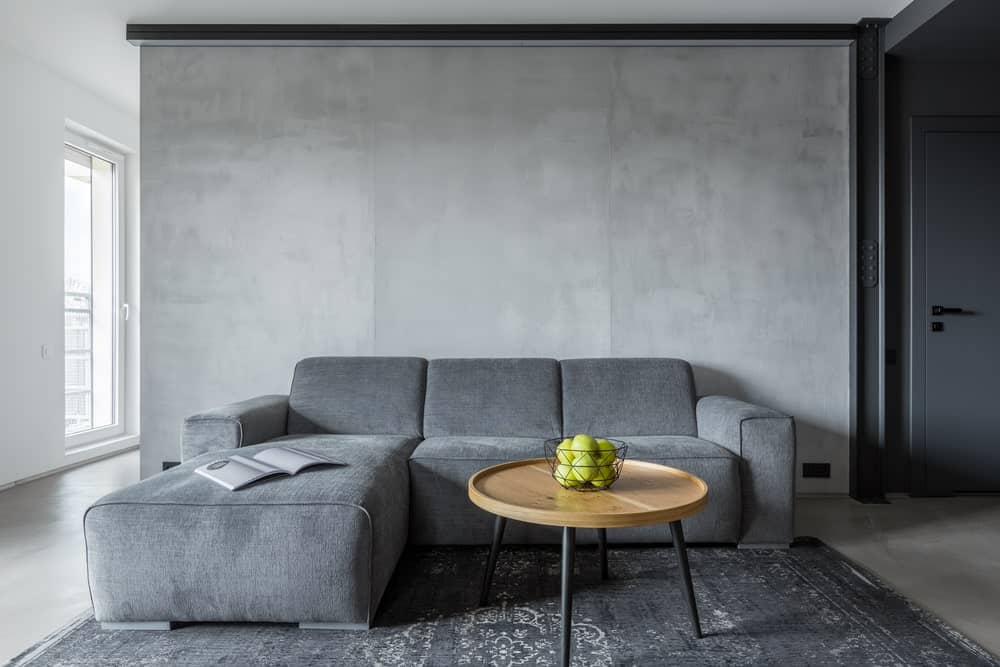 The massive L-shaped gray sofa looks so inviting in its dominance of this cozy gray living room. The white flooring is topped with a worn dark gray area rug that complements the light gray walls. This makes the wooden circular coffee table pop out.
