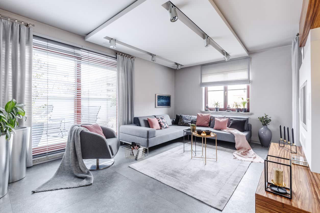 This living area features gray floors matching the gray set of seats with a pink accent. The room is lighted by track ceiling lights.