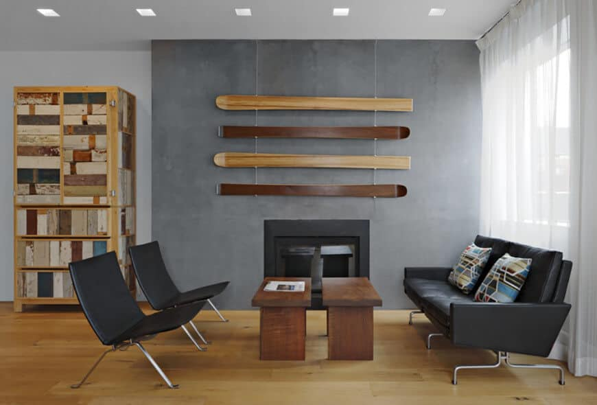 A small living space featuring a gray wall with a fireplace along with black seats and a pair of wooden center tables.