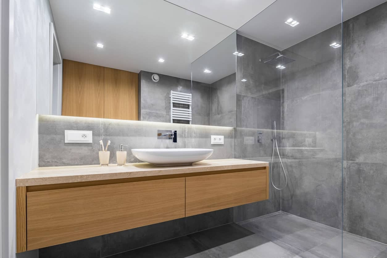 Medium-sized primary bathroom featuring a floating vanity with a single vessel sink and a walk-in shower room surrounded by large gray tiles walls and floors.