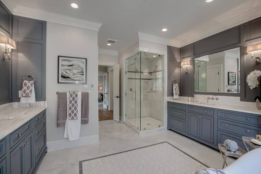Spacious gray primary bathroom featuring classy sink counters with marble countertops along with a freestanding tub and a walk-in shower room.