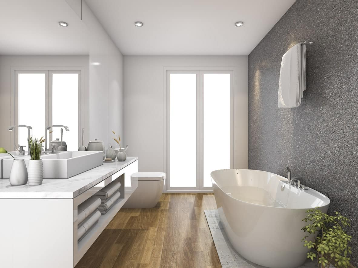 This primary bathroom features a gray wall and hardwood flooring. There's a floating vanity with a vessel sink along with a freestanding tub.