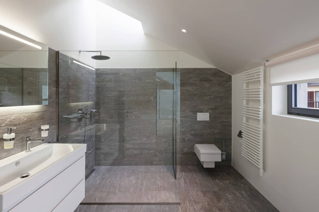 Gray-themed primary bathroom featuring a floating vanity sink and a large walk-in shower room.