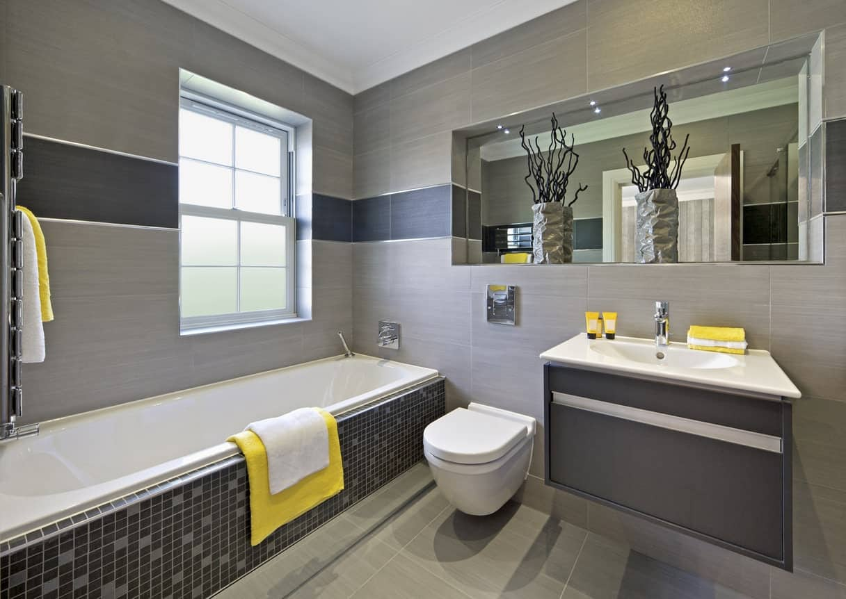 Medium-sized primary bathroom featuring a deep soaking tub, a floating vanity sink and a walk-in shower room surrounded by gray walls with a yellow accent.