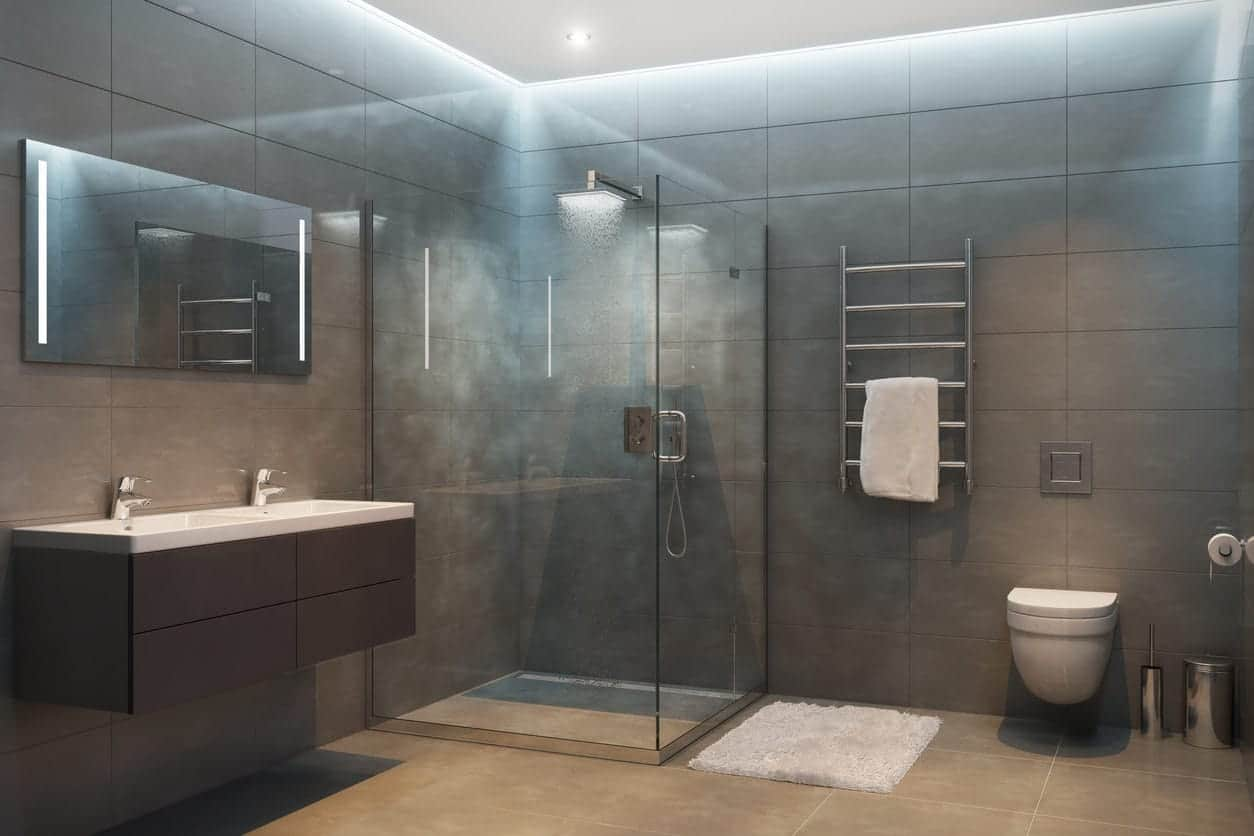 A large primary bathroom featuring a floating vanity with a double sink and a walk-in shower room surrounded by gray tiles walls and floors.