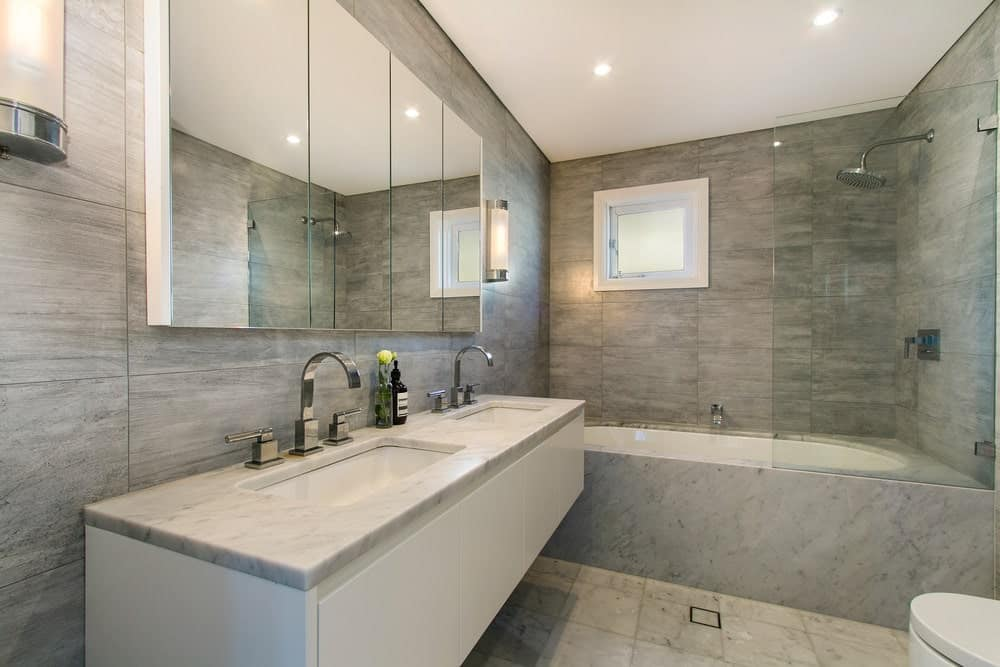 Gray master bathroom featuring a floating vanity with a double sink along with a shower and tub combo.