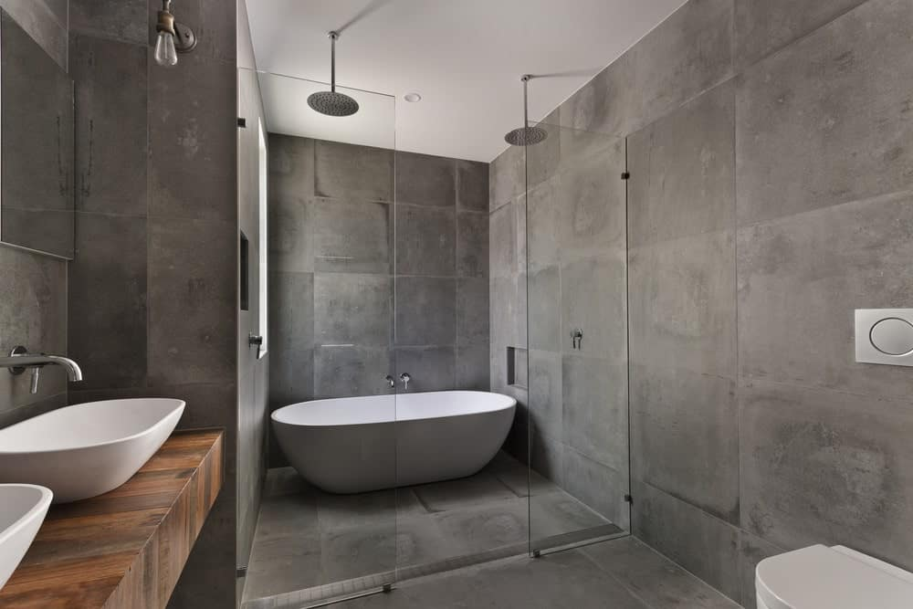 This gray primary bathroom offers two vessel sinks and a freestanding tub along with an open shower.