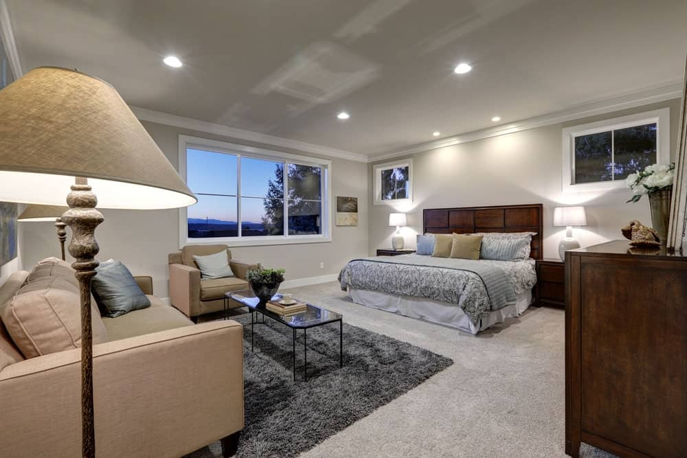 Spacious primary bedroom with its own living space featuring a couch and a chair set on the gray carpet flooring.