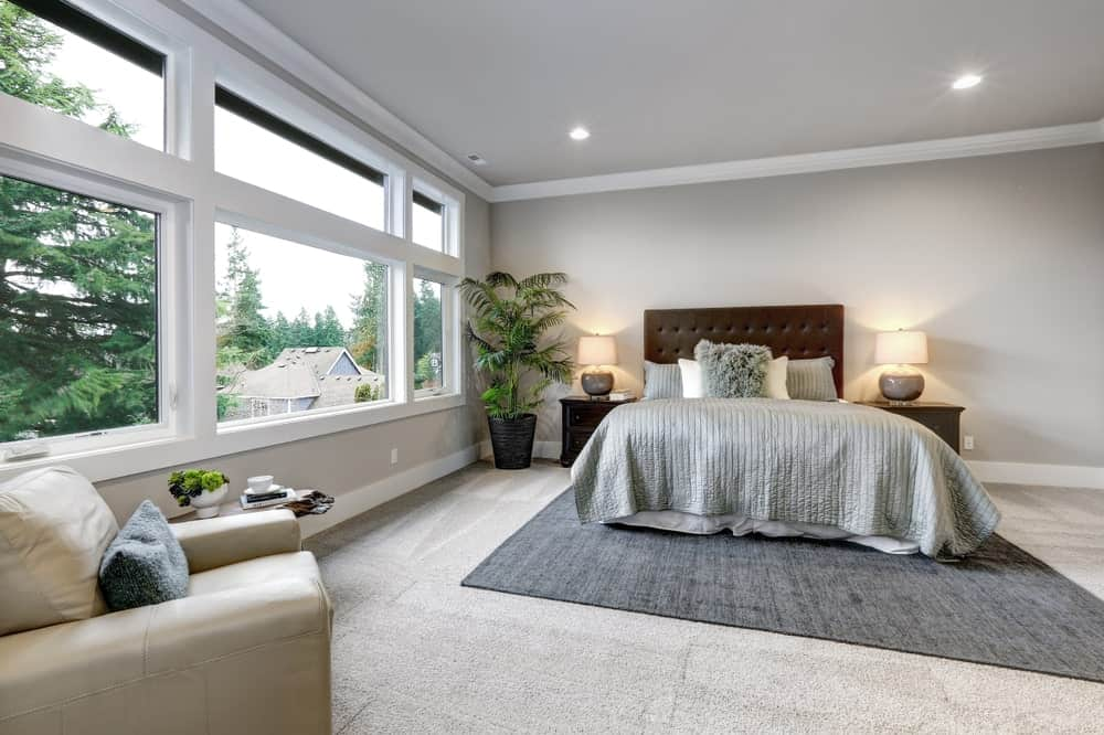 The brown cushioned headboard of the traditional bed is flanked by two lamps on identical wooden bedside drawers. This setup perfectly contrasts the light gray walls and ceiling lined with white moldings. These moldings pair well with the white frames of the wide windows.