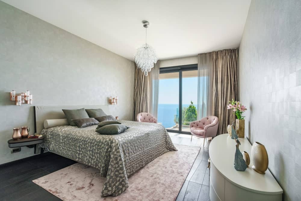 The lovely gray walls, gray bed sheets, and dark flooring are a perfect background for the elegant crystal pendant light hanging over the bed. underneath the bed is a cotton candy area rug that matches the pair of cushioned armchairs flanking the tall glass sliding doors.
