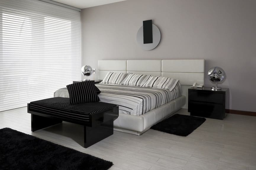 Modern master bedroom featuring gray walls and floors added by a black accent.