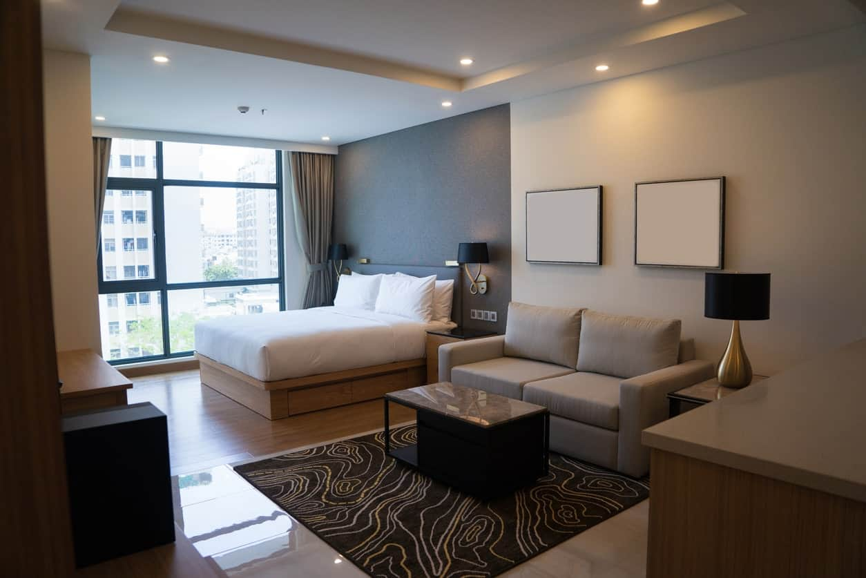 Gray master bedroom featuring its own small living space with a stylish set of black lamps.