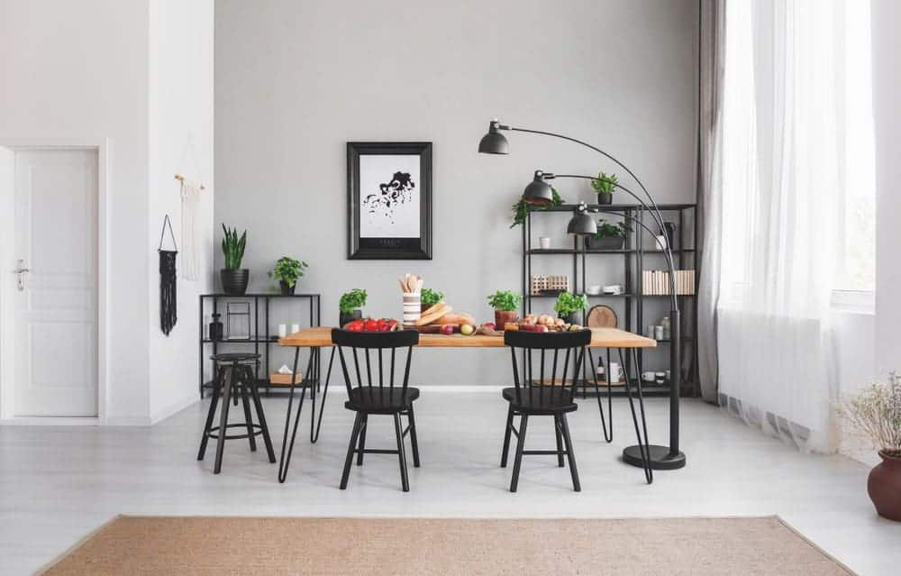 A gray dining room with a black accent. It features a wood-top dining table along with black seats and a black floor lamp.