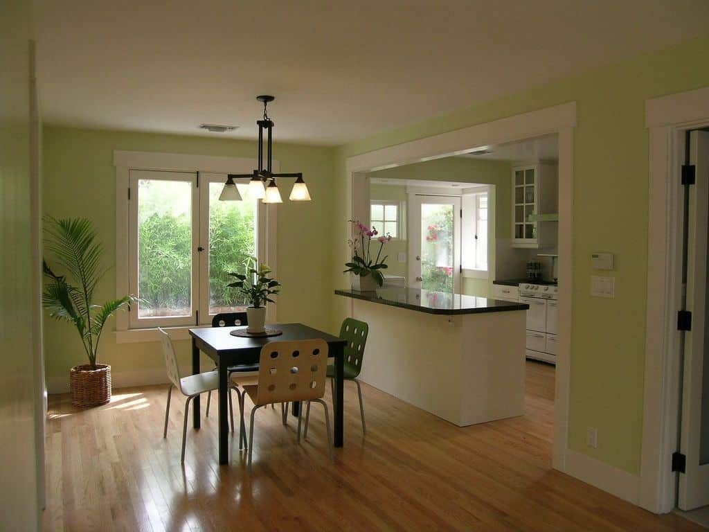 A dine-in kitchen with potted indoor plants and is surrounded by green walls. The room also features hardwood flooring.