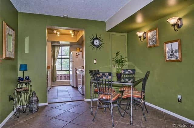 This dining area featuring green walls with two wall sconces. There's a square dining table set for four.