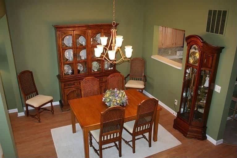 A small dining area featuring a dining table set for four lighted by a gorgeous chandelier.