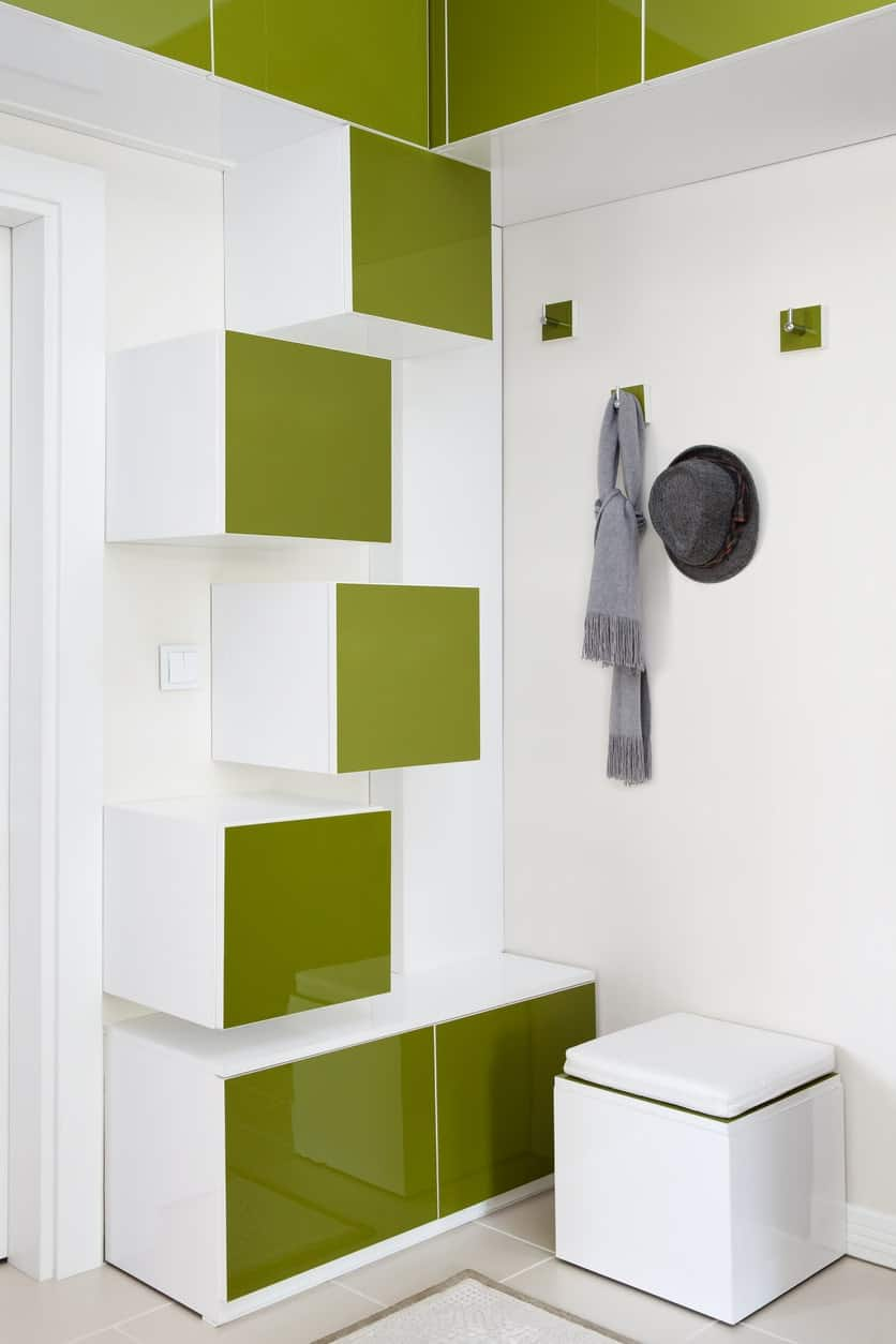 This is a spectacular foyer that is a result of the combination of green and white sleek elements that reflect the brightness of the room and the square green panels extend all the way to the ceiling. There are modern built-in cabinets for storage with similar avocado green facades that match the paneling of the wall-mounted hooks for the coats and hats.