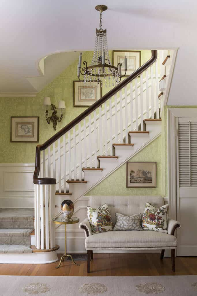 This traditional and welcoming foyer has light green walls with subtle intricate patterns that work well as a background for the wall-mounted artworks. The lower half of these green walls have a white wooden finish that matches with the light gray cushioned sofa by the stairs.
