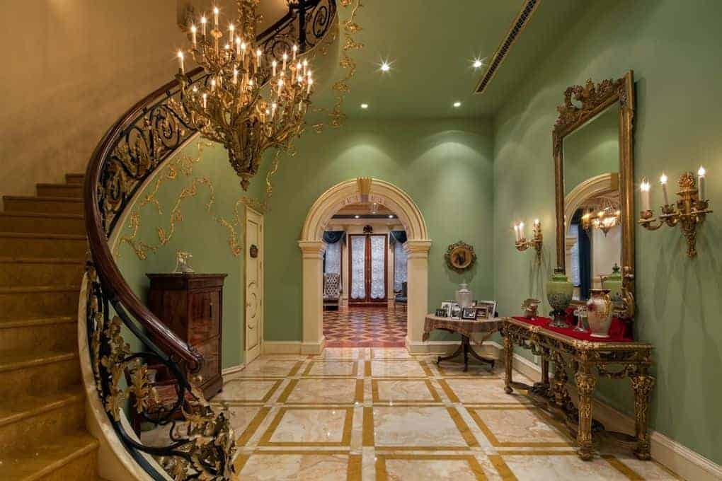 The pastel green hue of the walls and high ceiling are a great colorful background for the royal treatment of golden elements scattered in the area. There are golden vines on the walls, golden candelabra-style wall-mounted lights that match the majestic golden chandelier over gold-trimmed marble floors.