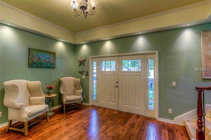 This is a simple and inviting foyer with a couple of gray cushioned armchairs against the pastel green wall flanking a small circular table with a wall-mounted flower painting above. The beige ceiling works well with the green walls and has a dark iron chandelier in the middle.