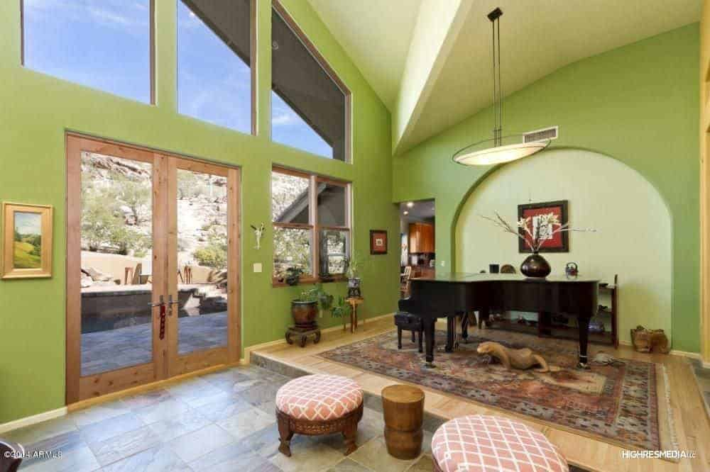 This is an eclectic grand foyer with a high arched ceiling complemented by immense transom windows. The foyer has double glass doors that pair well with the delightful green walls. The eclectic details that adorn the grand piano gives this foyer a homey warmth.