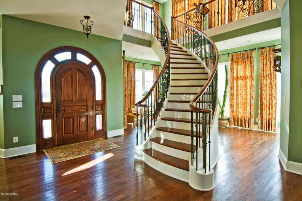 The wooden main door of this airy foyer has an arched top that is followed by the sidelights that form an arch over the door. This is properly contrasted by the pastel green hue of the walls that matches well with the white ceiling. The hardwood flooring is topped with a colorful patterned rug that serves as a welcome mat.