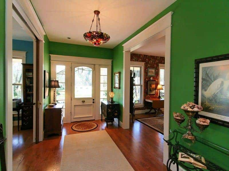 The bright green walls of this foyer offer a memory of a forest against the earthly representation of the hardwood flooring and finally, the white ceiling is the bright skies that has a shiny stained-glass dome light. The entrance is flanked by two distinct wooden console tables that contrasts the white main door.