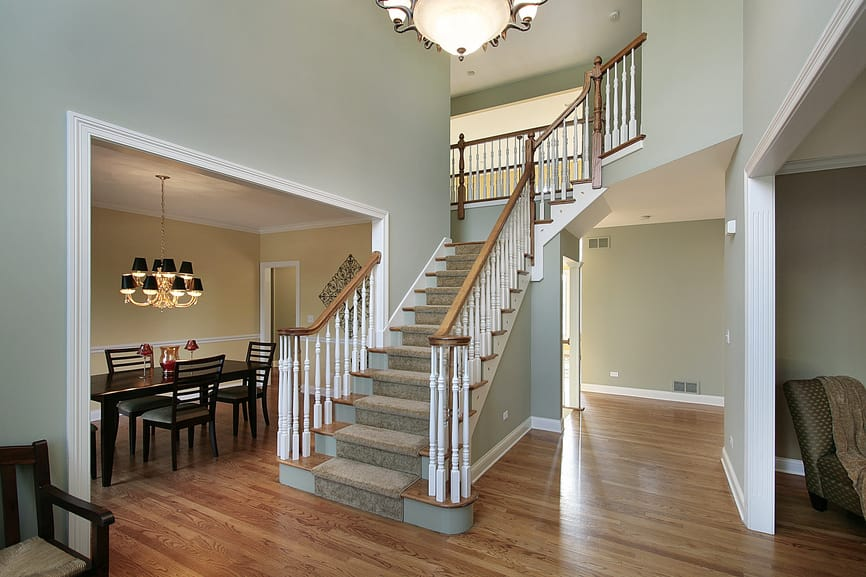 Minimalist foyer featuring hardwood flooring and green walls, along with carpeted staircase steps.