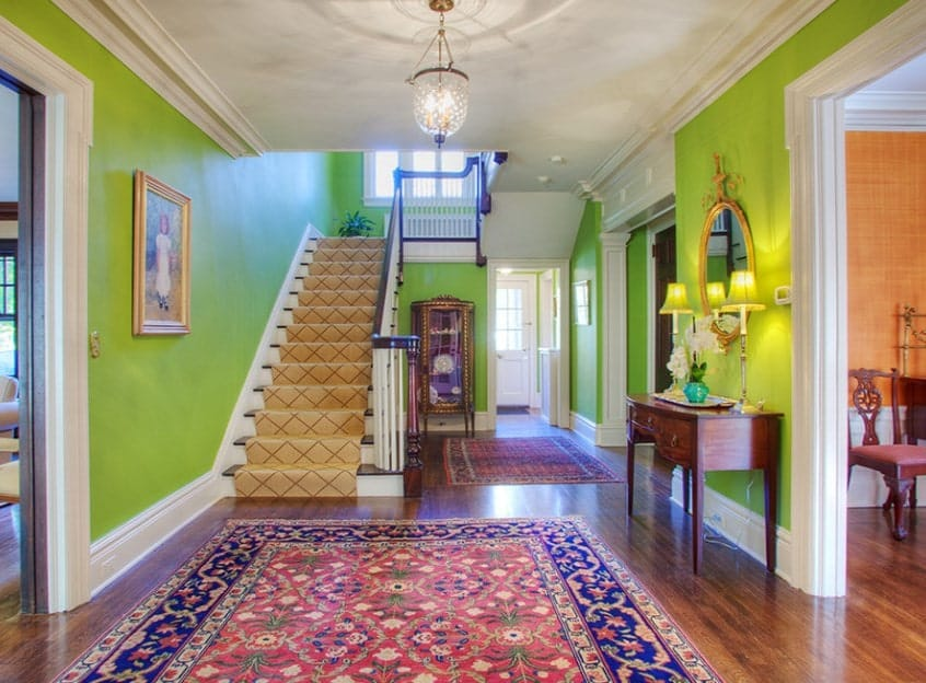 A green foyer featuring hardwood floors topped by a large classy rug along with carpeted staircase.